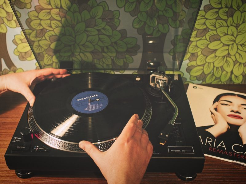 a person putting the vinyl on the vintage turntable