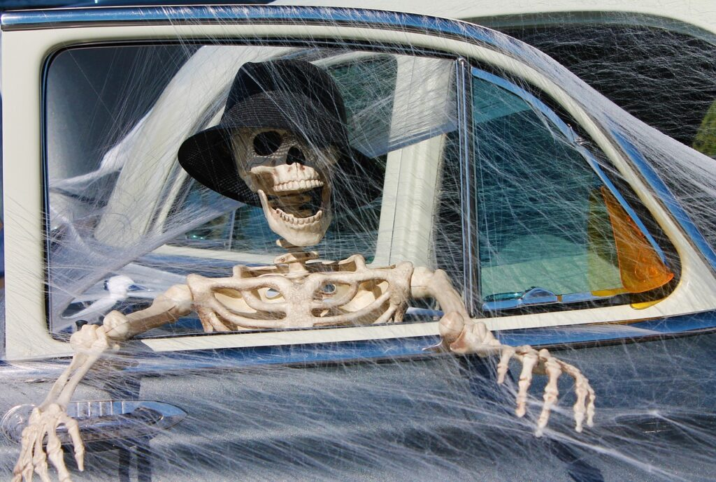 Halloween skeleton in a vintage automobile covered with cobwebs