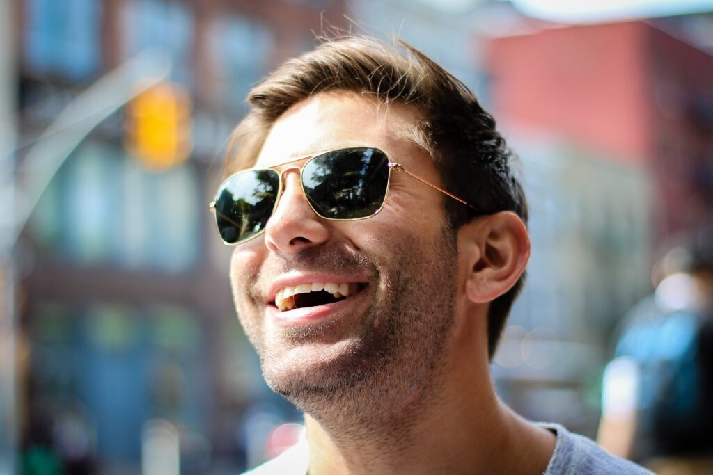 A man in the city smiling and wearing sunglasses