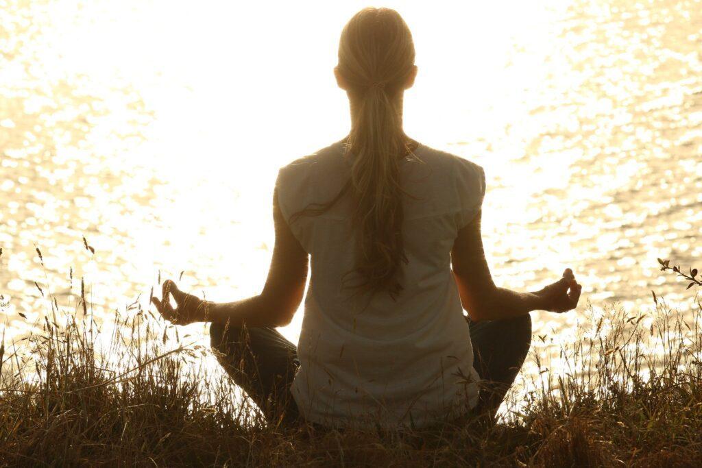 A woman meditates beside a lake